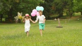 Το μικρό παιδί κρατά το κορίτσι από το χέρι και τρέχουν κατά μήκος του χορτοτάπητα από κοινού κίνηση αργή φιλμ μικρού μήκους