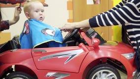 Το μικρό παιδί κόβει τον κουρέα Κάθεται σε μια καρέκλα που μοιάζει με ένα αυτοκίνητο Το Mom αυτό αποσπά και παίζει με τον φιλμ μικρού μήκους