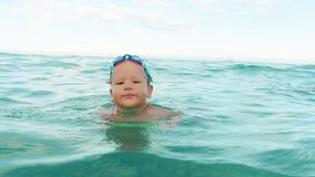 Το μικρό παιδί με κολυμπά τον πίνακα σε αργή κίνηση φιλμ μικρού μήκους
