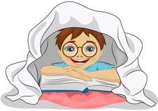 Το μικρό παιδί με τα γυαλιά διαβάζει ένα βιβλίο στο κρεβάτι κάτω από το κάλυμμα Στοκ Εικόνες