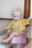Το μικρό παιδί 8 μηνών κάθεται σε ένα δοχείο στοκ φωτογραφία