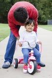 Το μικρό παιδί οδηγά ένα ποδήλατο με τον πατέρα Στοκ Φωτογραφία