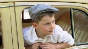 Το μικρό παιδί οδηγεί το μεγάλο αναδρομικό αυτοκίνητο φιλμ μικρού μήκους