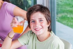 Το μικρό παιδί πίνει το ευτυχές χαμόγελο χυμού από πορτοκάλι, κάθισμα Στοκ φωτογραφία με δικαίωμα ελεύθερης χρήσης