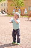 Το μικρό παιδί πίνει το νερό από ένα μπουκάλι στοκ εικόνα
