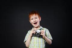 Το μικρό παιδί παίρνει τη φωτογραφία με την εκλεκτής ποιότητας κάμερα στο μαύρο υπόβαθρο Στοκ φωτογραφία με δικαίωμα ελεύθερης χρήσης
