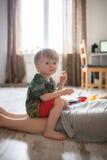 Το μικρό παιδί παιδιών μικρών παιδιών παίζει στο σπίτι κοντά mom Στοκ Φωτογραφίες