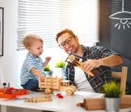 Το μικρό παιδί πατέρων και γιων συλλέγει την τέχνη ένα αυτοκίνητο από το ξύλο και το παιχνίδι Στοκ Φωτογραφία
