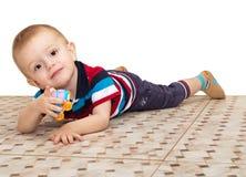Το μικρό παιδί, που βρίσκεται σε ένα πάτωμα, παιχνίδια με το αυτοκίνητο παιχνιδιών και το POI Στοκ Φωτογραφία