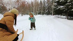 Το μικρό παιδί προσπαθεί στο έλκηθρο και το γέλιο φιλμ μικρού μήκους