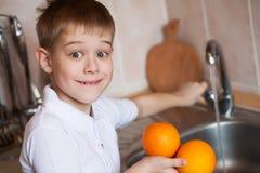 Το μικρό παιδί πλένει τα φρούτα στην κουζίνα Στοκ φωτογραφία με δικαίωμα ελεύθερης χρήσης