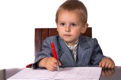 Το μικρό παιδί σε ένα επιχειρησιακό κοστούμι υπογράφει τα έγγραφα Στοκ Εικόνες