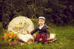 Το μικρό παιδί σε ένα σακάκι και ένα καρό ασθμαίνει να καθίσει στο μαξιλάρι, ΝΕ Στοκ Φωτογραφία