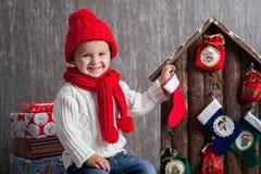 Το μικρό παιδί στα Χριστούγεννα, άνοιγμα παρουσιάζει Στοκ Φωτογραφίες
