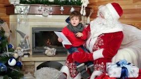 Το μικρό παιδί στην περιτύλιξη santa ` s που λέει τα Χριστούγεννά του επιθυμεί, παιδί που επισκέπτεται τη χειμερινή κατοικία Αγίο απόθεμα βίντεο