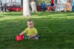 Το μικρό παιδί στη χλόη με έναν πλαστικό κάδο Στοκ εικόνα με δικαίωμα ελεύθερης χρήσης