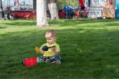 Το μικρό παιδί στη χλόη με έναν πλαστικό κάδο Στοκ Φωτογραφία