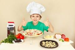 Το μικρό παιδί στο καπέλο αρχιμαγείρων απολαμβάνει την πίτσα Στοκ Εικόνα