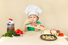 Το μικρό παιδί στο καπέλο αρχιμαγείρων βάζει τις ελιές στην κρούστα πιτσών Στοκ Εικόνες