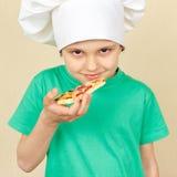 Το μικρό παιδί στο καπέλο αρχιμαγείρων πρόκειται να δοκιμάσει τη μαγειρευμένη πίτσα Στοκ φωτογραφία με δικαίωμα ελεύθερης χρήσης
