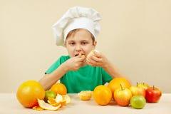 Το μικρό παιδί στο καπέλο αρχιμαγείρων τρώει το φρέσκο πορτοκάλι στον πίνακα με τα φρούτα Στοκ Φωτογραφία