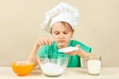 Το μικρό παιδί στο καπέλο αρχιμαγείρων χύνει τη ζάχαρη για το κέικ ψησίματος στοκ φωτογραφία