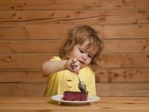 Το μικρό παιδί τρώει το κέικ φρούτων Στοκ Φωτογραφία