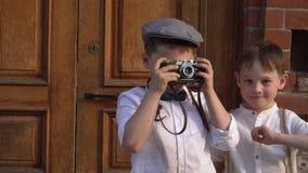 Το μικρό παιδί φωτογραφίζει τη κάμερα σε έναν αναδρομικό, οι δαπάνες αγοριών με έναν αναδρομικό η κάμερα φιλμ μικρού μήκους