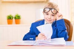 Το μικρό παιδί χαμογελά καθμένος στο γραφείο Στοκ Εικόνες
