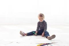 Το μικρό παιδί χρωματίζει μια εικόνα των κραγιονιών Στοκ Εικόνα