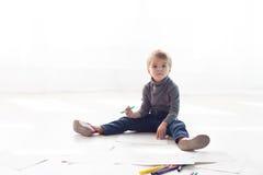 Το μικρό παιδί χρωματίζει μια εικόνα των κραγιονιών Στοκ Εικόνες