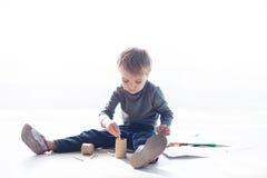 Το μικρό παιδί χρωματίζει μια εικόνα των κραγιονιών Στοκ Φωτογραφία