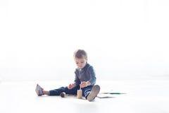 Το μικρό παιδί χρωματίζει μια εικόνα των κραγιονιών Στοκ φωτογραφία με δικαίωμα ελεύθερης χρήσης