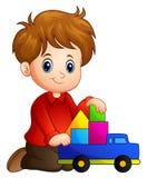 Το μικρό παιδί χτίζει ένα σπίτι από τους φραγμούς με το φορτηγό παιχνιδιών απεικόνιση αποθεμάτων