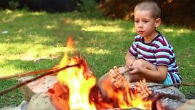 Το μικρό παιδί ψήνει το μπέϊκον απόθεμα βίντεο