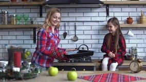 Το μικρό χαριτωμένο κορίτσι κάθεται στην κορυφή κουζινών και η νέα ξανθή μητέρα ψήνει τα μπισκότα και τα αφαιρεί από το φούρνο απόθεμα βίντεο