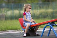 Το μικρό χαριτωμένο νέο ξανθό κορίτσι παιδιών κάθεται ευμετάβλητο, 0 και ανικανοποίητος επάνω δείτε την ταλάντευση πριονιών τη θε στοκ εικόνα με δικαίωμα ελεύθερης χρήσης