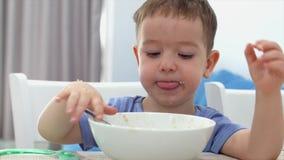 Το μικρό χαριτωμένο παιδί κάθεται σε έναν πίνακα και τρώει oatmeal του, το μωρό τρώει πρόθυμα Ευτυχής παιδική ηλικία έννοιας απόθεμα βίντεο