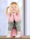 Το μικρό smily κορίτσι κάθεται σε έναν ασήμαντο στοκ εικόνες με δικαίωμα ελεύθερης χρήσης
