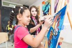 Το μικτό μικρό κορίτσι φυλών με έναν δάσκαλο στην ομάδα προσχολικού σπουδαστή κάθισε το σχέδιο μια εικόνα Ζωγραφική στο maelbert στοκ φωτογραφίες με δικαίωμα ελεύθερης χρήσης