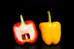 Το μισό από το πιπέρι στο καθαρό μαύρο υπόβαθρο Κίτρινα και κόκκινα πιπέρια που κόβονται στο μισό Στοκ Εικόνες