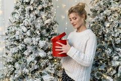 Το μισό πορτρέτο μήκους του νέου όμορφου ξανθού κοριτσιού ανοίγει το δώρο με το ενδιαφέρον στοκ εικόνα