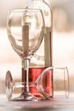 Το μισό πλήρες μπουκάλι δύο γυαλιών αυξήθηκε κατακόρυφος φωτός της ημέρας κρασιού στοκ φωτογραφία με δικαίωμα ελεύθερης χρήσης