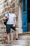 Το μοντέρνο άτομο τουριστών έντυσε σε ένα άσπρο πουκάμισο και τα σορτς με το σακίδιο πλάτης πέρα από τον ώμο του Στάση στα βήματα Στοκ φωτογραφία με δικαίωμα ελεύθερης χρήσης