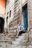 Το μοντέρνο άτομο τουριστών έντυσε σε ένα άσπρο πουκάμισο και τα σορτς με το σακίδιο πλάτης πέρα από τον ώμο του Κάθισμα στα βήμα Στοκ Εικόνα