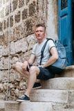 Το μοντέρνο άτομο τουριστών έντυσε σε ένα άσπρο πουκάμισο και τα σορτς με το σακίδιο πλάτης πέρα από τον ώμο του Κάθισμα στα βήμα Στοκ Εικόνες