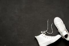 Το μοντέρνο επίπεδο βάζει των άσπρων πάνινων παπουτσιών στο μαύρο υπόβαθρο Στοκ φωτογραφία με δικαίωμα ελεύθερης χρήσης
