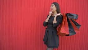 Το μοντέρνο θηλυκό αγοραστών με τις συσκευασίες σκέφτεται τι για να αγοράσει στην εποχιακή πώληση τη μαύρη Παρασκευή απόθεμα βίντεο
