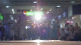 Το μοντέρνο θηλυκό πρότυπο στην εξέδρα περιπάτων κοστουμιών κατά τη διάρκεια της επίδειξης μόδας στο φωτισμό στο υπόβαθρο θόλωσε  απόθεμα βίντεο