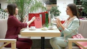 Το μοντέρνο θηλυκό Shopaholics πίνει το τσάι στον καφέ μετά από αγοράζει μέσα τις εποχιακές πωλήσεις και τις εκπτώσεις στη μαύρη  απόθεμα βίντεο
